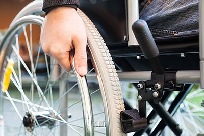 man in a wheelchair with hand on the wheel | Grand Junction Nursing Home Death