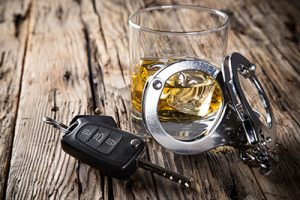 glass of booze next to car keys and handcuffs | Drunk Driving and Teens