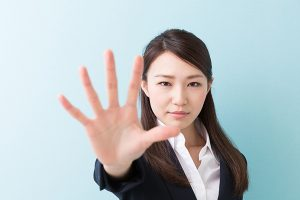 young woman holding out hand in stop gesture | Sexual Assault Victims Rights Attorneys