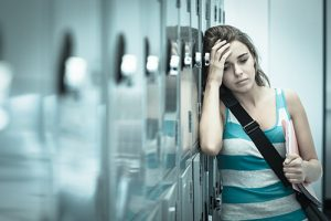 sad college aged woman leaning against a row of lockers | Campus Sexual Assault Attorneys