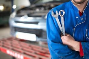 mechanic in shop holding tools | How to Get Your Car Repaired After an Accident