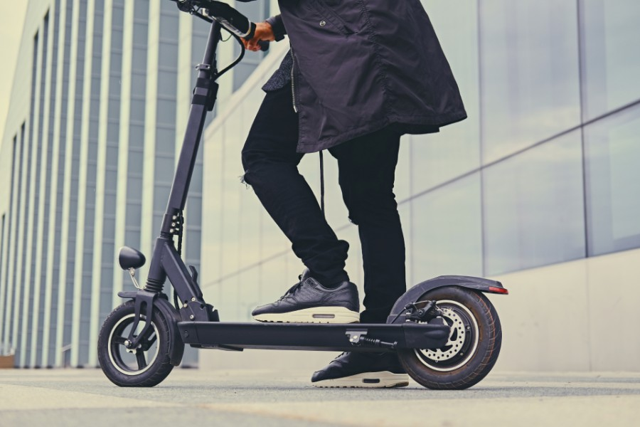 man wearing a jacket riding on an electric scooter | Electric Scooters Not Allowed on Sidewalks in Denver