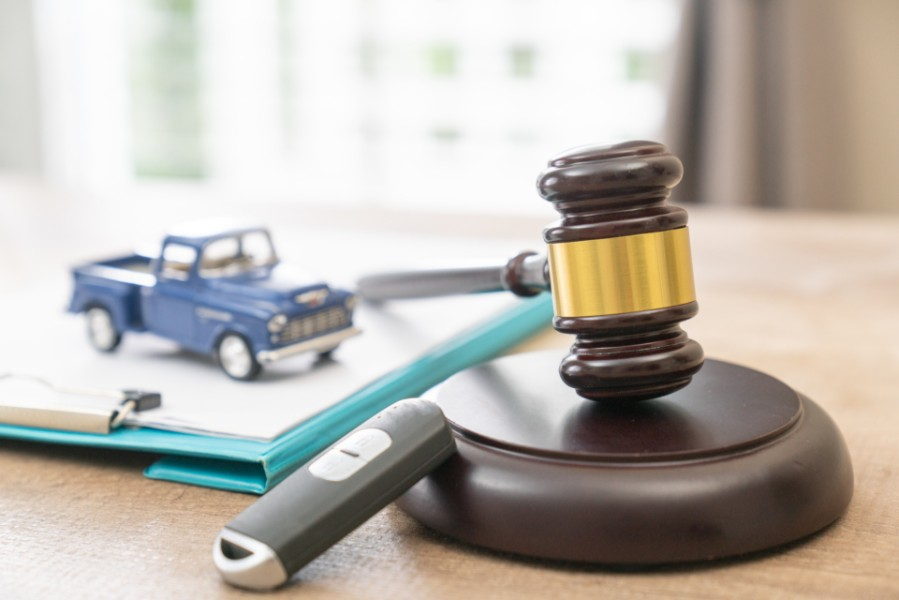 gavel beside a miniature car on top of a pile of documents | Colorado Hands Free Driving Bill