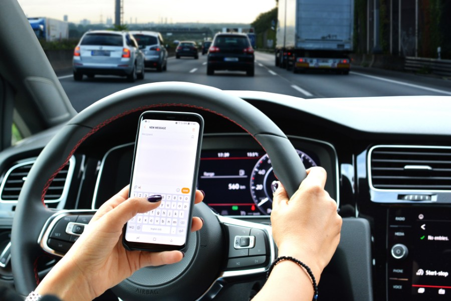 woman driving on the road while texting | distracted driving law in colorado