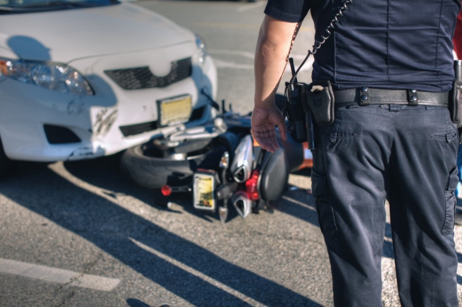 Police officer looking at an accident between a car and motorcycle | What to Do After a Motorcycle Accident in Denver