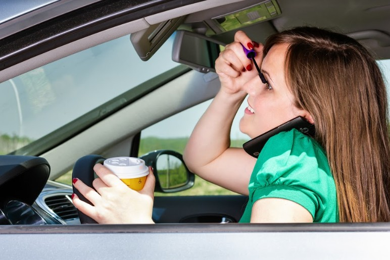 woman doing her make up while simultaneously drinking coffee and calling all the while driving a car | important automobile collision information you need to know
