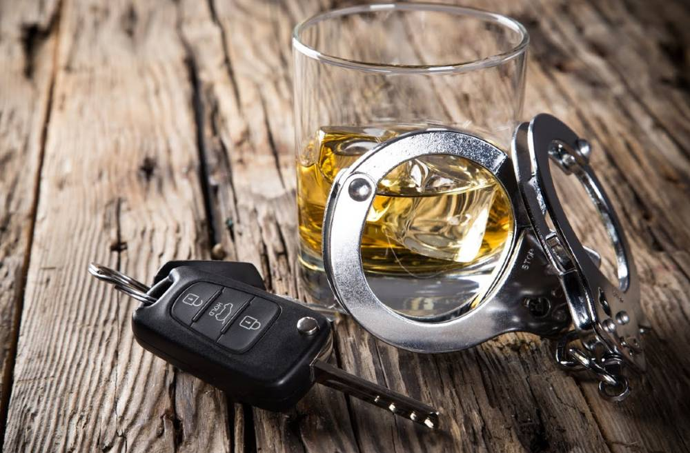 glass of alcohol with driver's key and handcuff | dui car accident on south academy boulevard