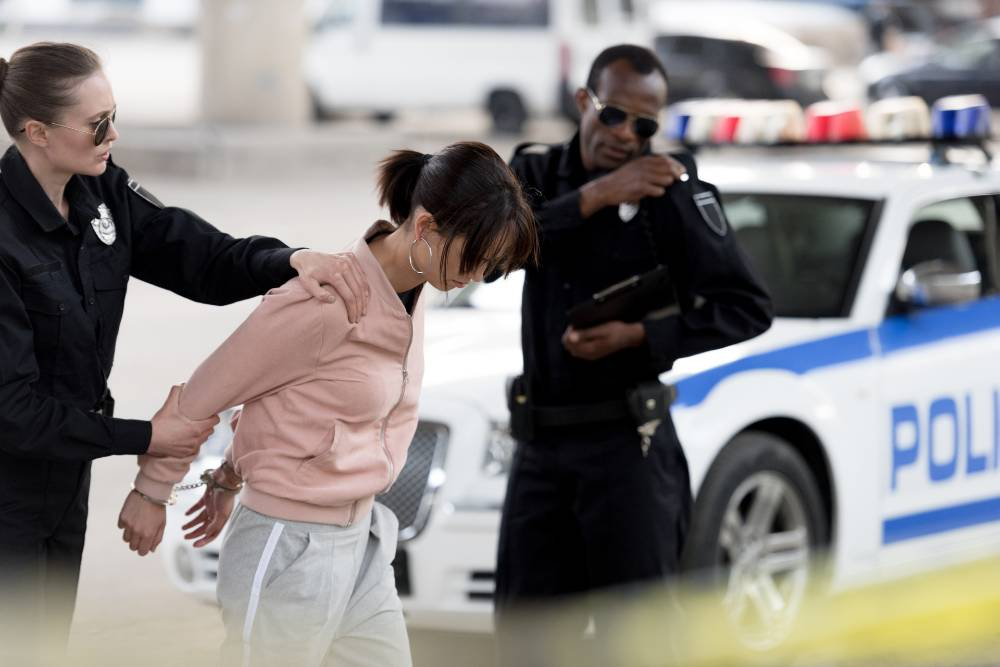 police woman holding a female suspect while her partner uses a radio | hit and run crash at 49th street and sheridan boulevard