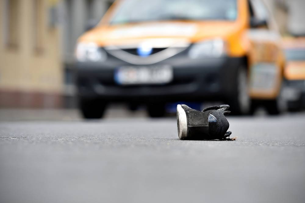 shoe left on the street following an accident with a car on the background | hit-and-run accident in five points