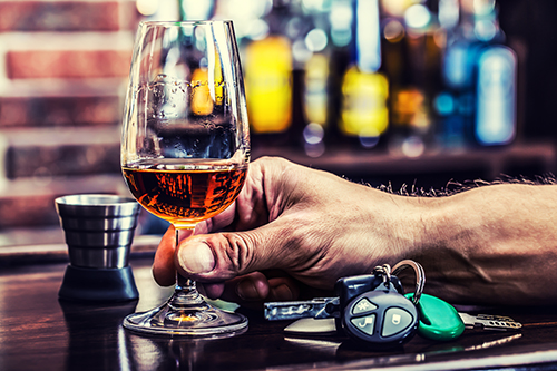 man holding glass of whiskey on bar with car keys