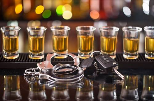 handcuffs and car keys with alcohol shots in the background | dui accident in pueblo