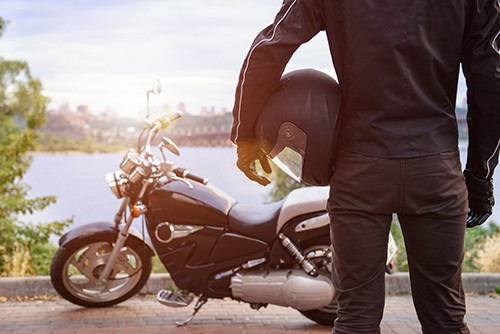 motorcyclist holding helmet and looking at bike | Fatal Motorcycle Collision in Frederick