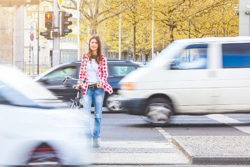 woman with bike crossing street with traffic